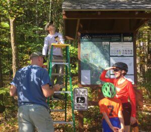 two men work on kiosk, one on a ladder. A woman and boy with bike helmets on stand asking man in blue shirt some questions.