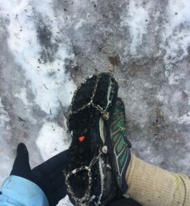Ice Trekkers on Shoes with ice and snow on ground. Shoe tilted to shoe sharp traction metal web on bottom of shoe.