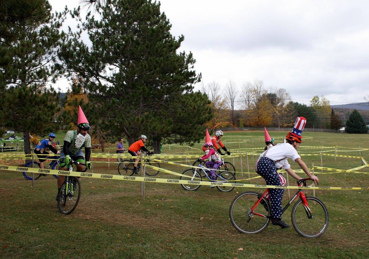 People dressed in costumes (Uncle Sam, knomes), on bicycles on a course marked with yellow tape